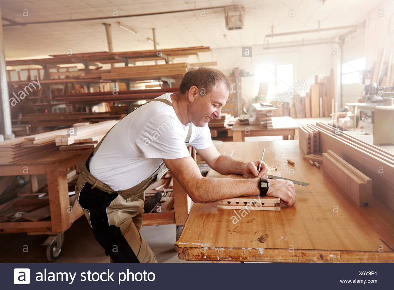 Male carpenter marking wood with pencil at workbench - Stock Image