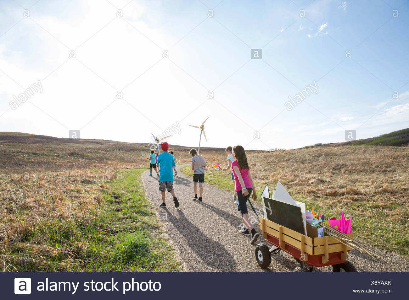 Children walking on path with wind turbines - Stock Image