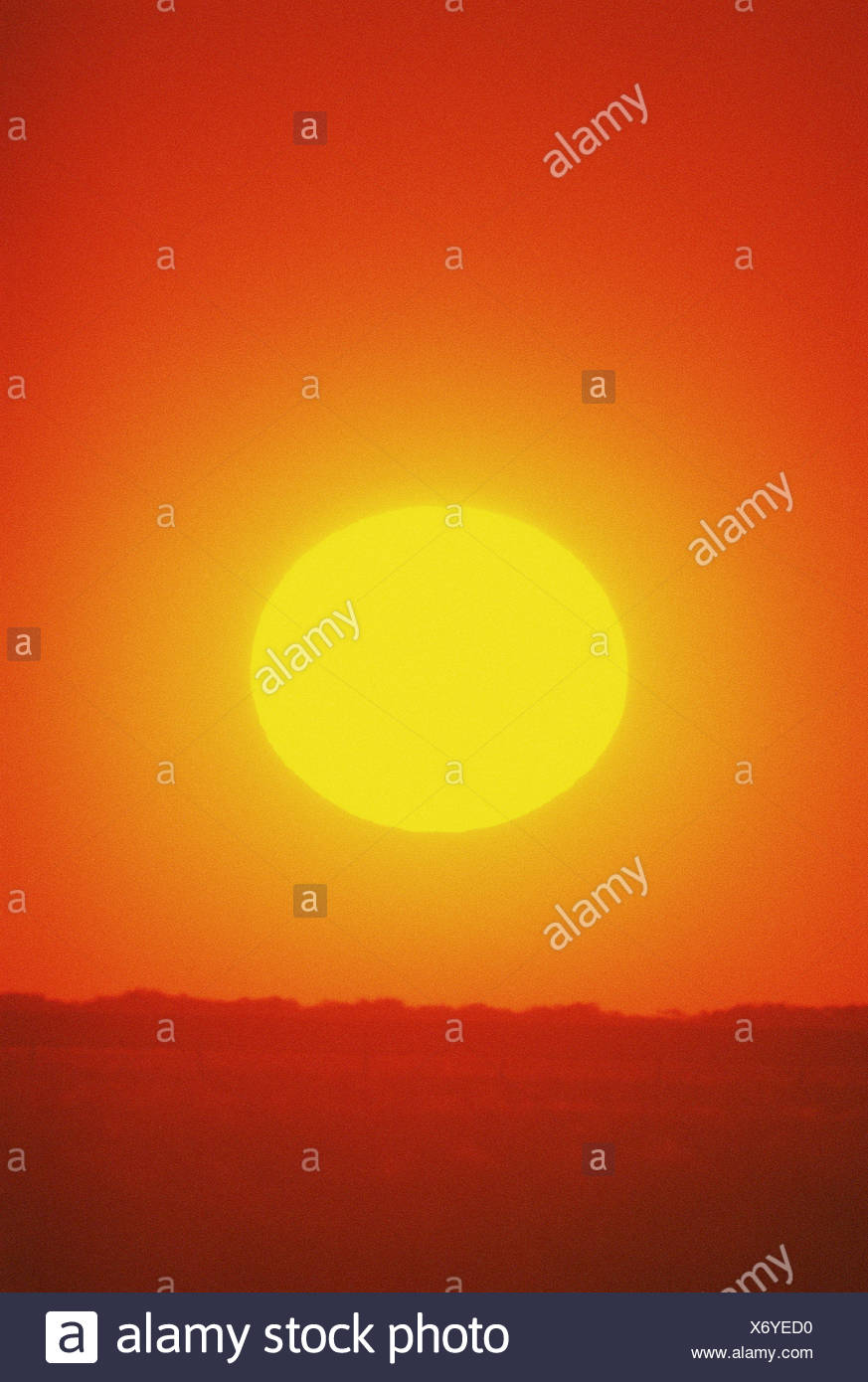Sunset. Sun setting over hilly horizon. - Stock Image
