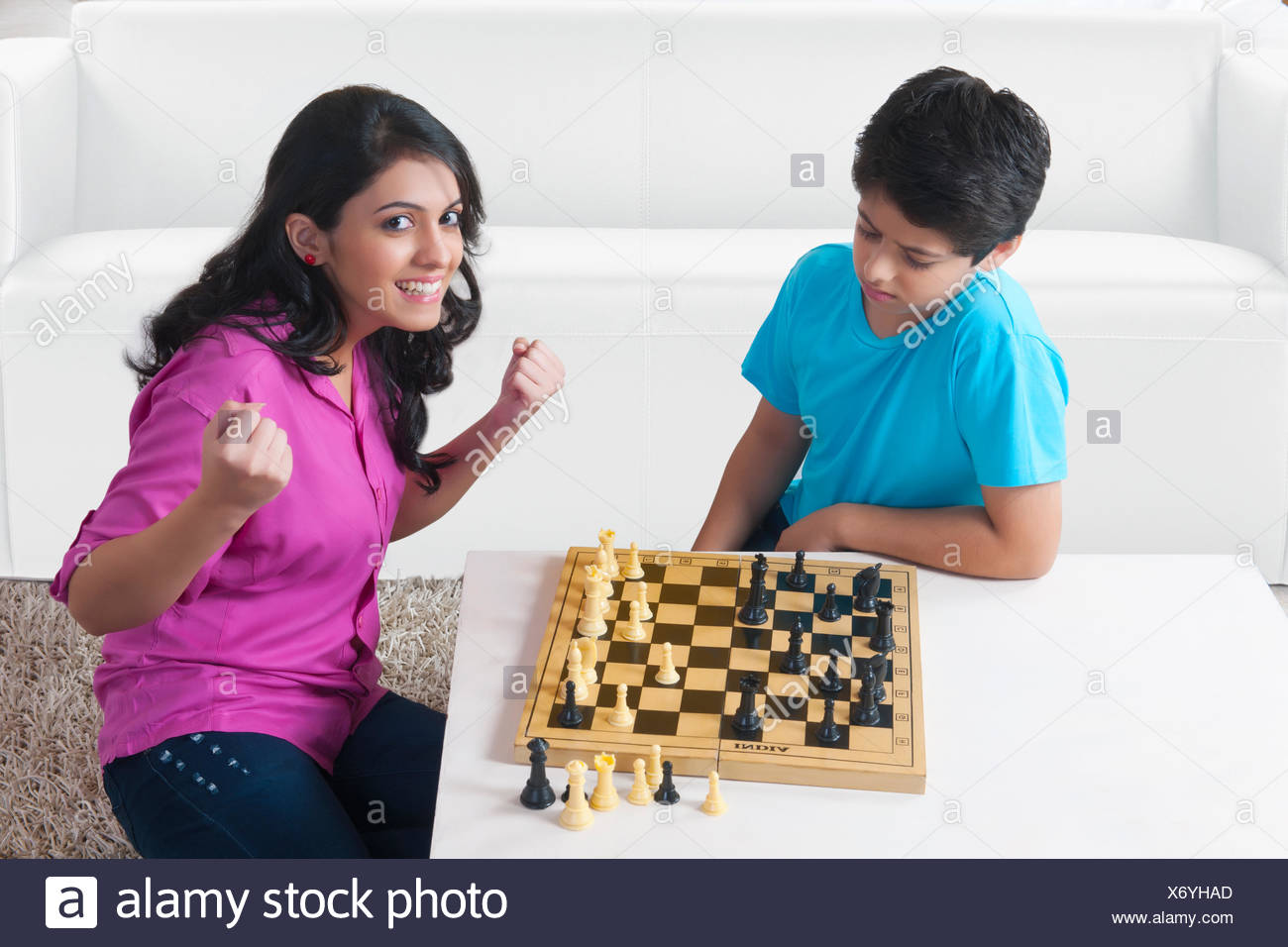 Sister and brother playing chess in living room - Stock Image