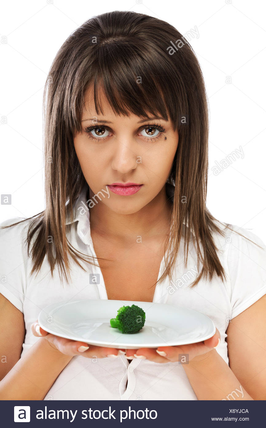 Young woman unhappy for eating healthy - Stock Image