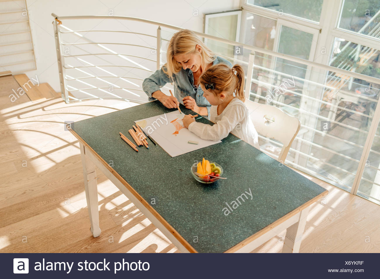 Mature woman and girl at home drawing together - Stock Image