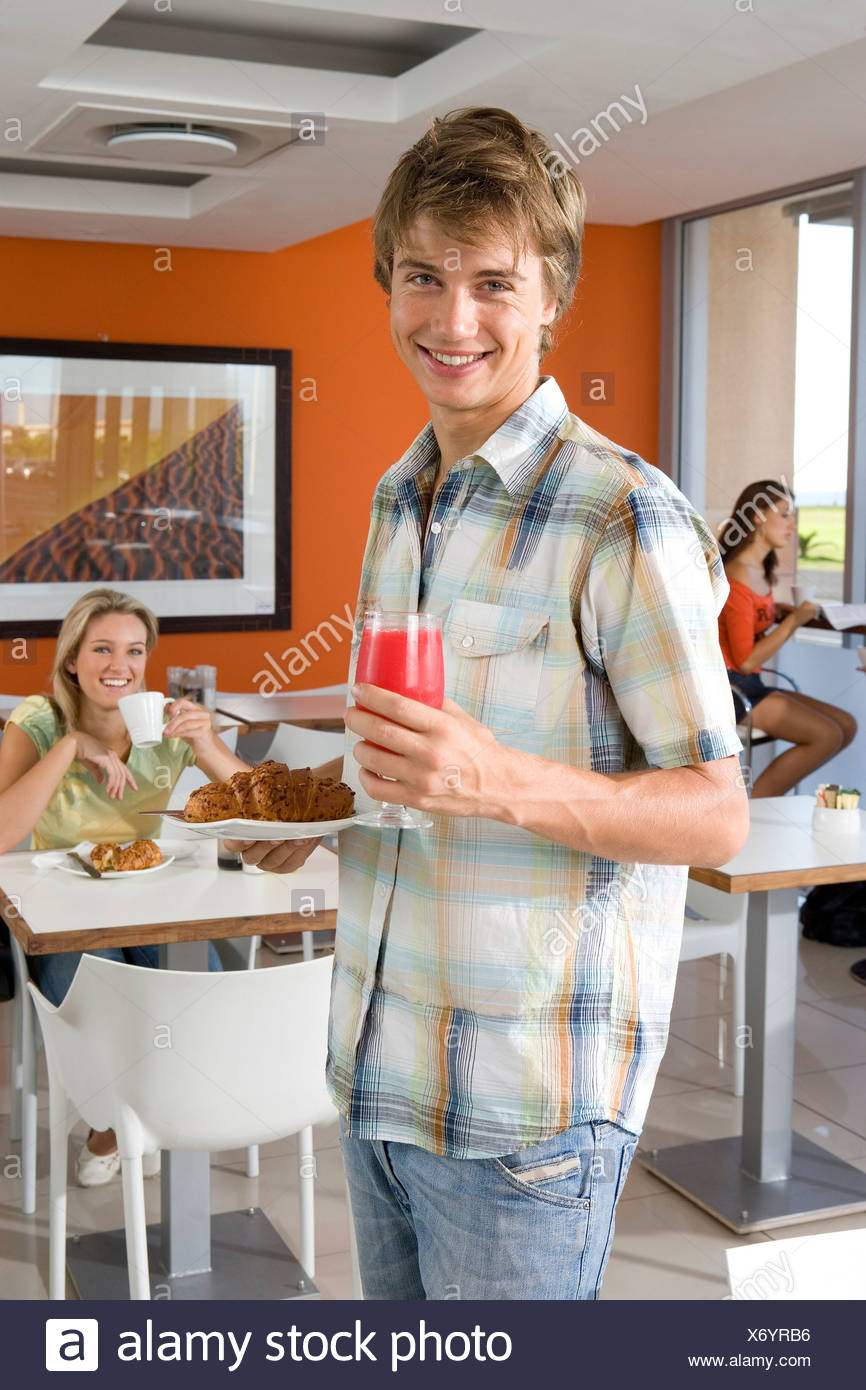 Young man holding plate of food in cafeteria, smiling, portrait, young woman smiling in background - Stock Image