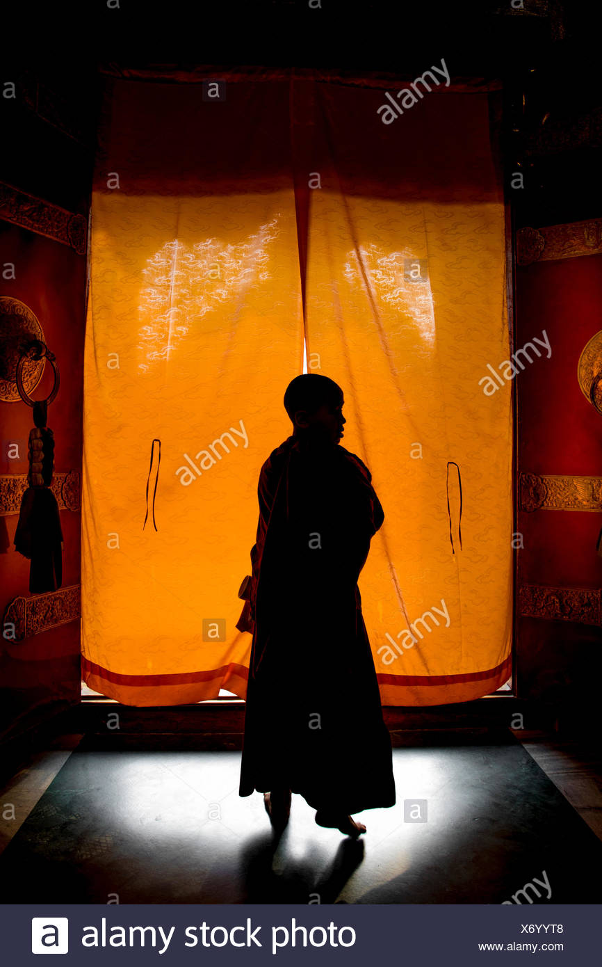 Silhouette of young monk leaving monastery in Boudhanath Temple, Kathmandu, Nepal - Stock Image