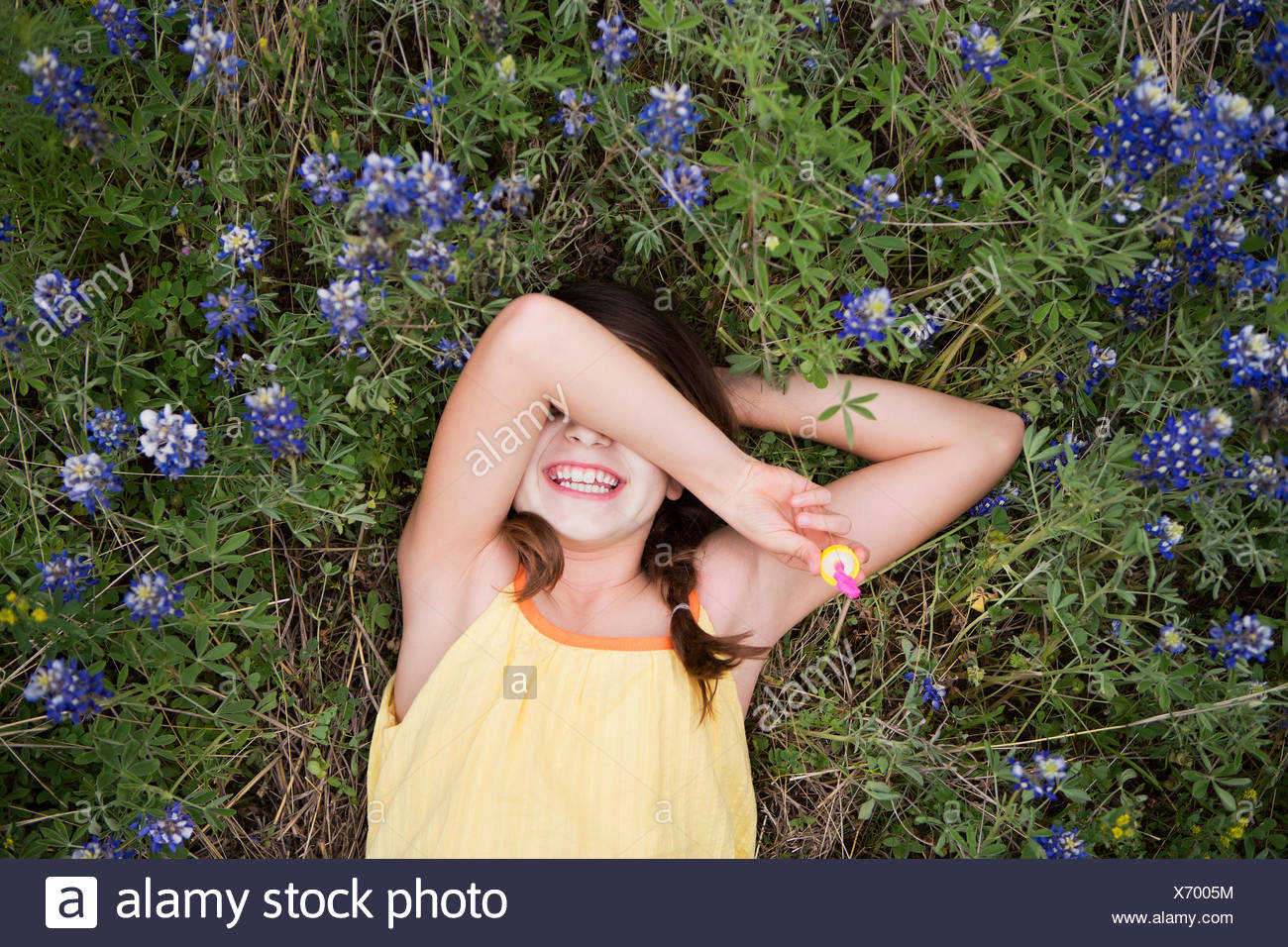 A young girl lying on her back with her arm over her eyes. - Stock Image