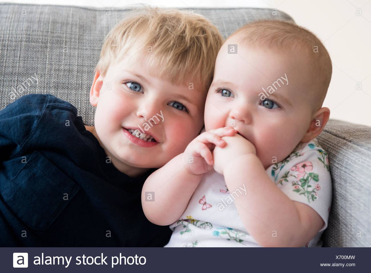 Boy (2-3) with baby sister (12-17 months) sitting on sofa - Stock Image