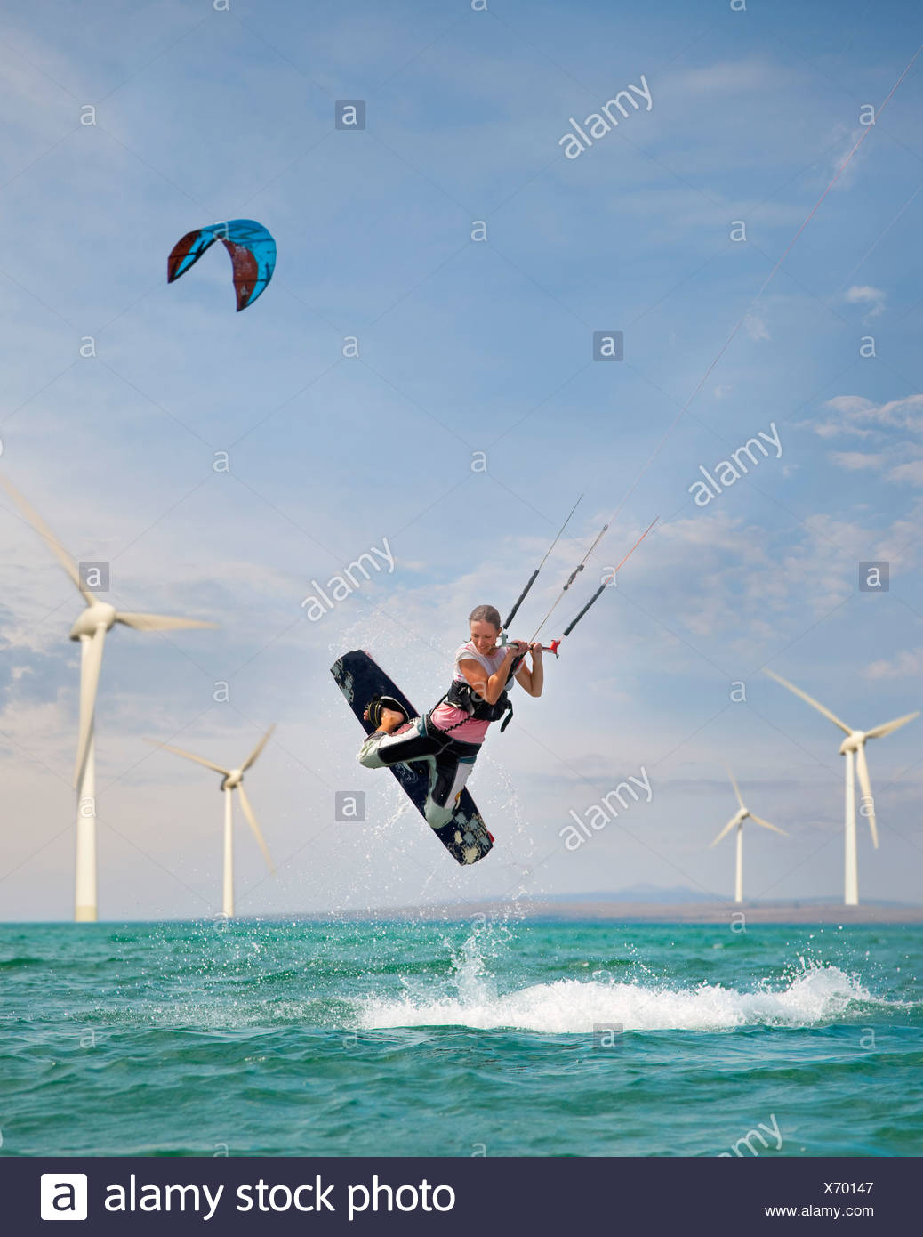 Croatia, Zadar, Kitesurfer jumping in front of wind turbine Stock Photo