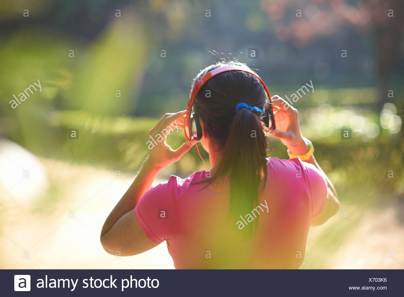 Rear view of mature woman with pony tail wearing headphones - Stock Image