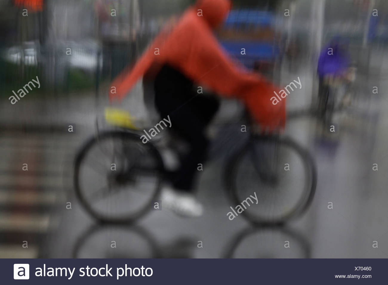 Bicyclist in the rain, Shanghai, China. - Stock Image
