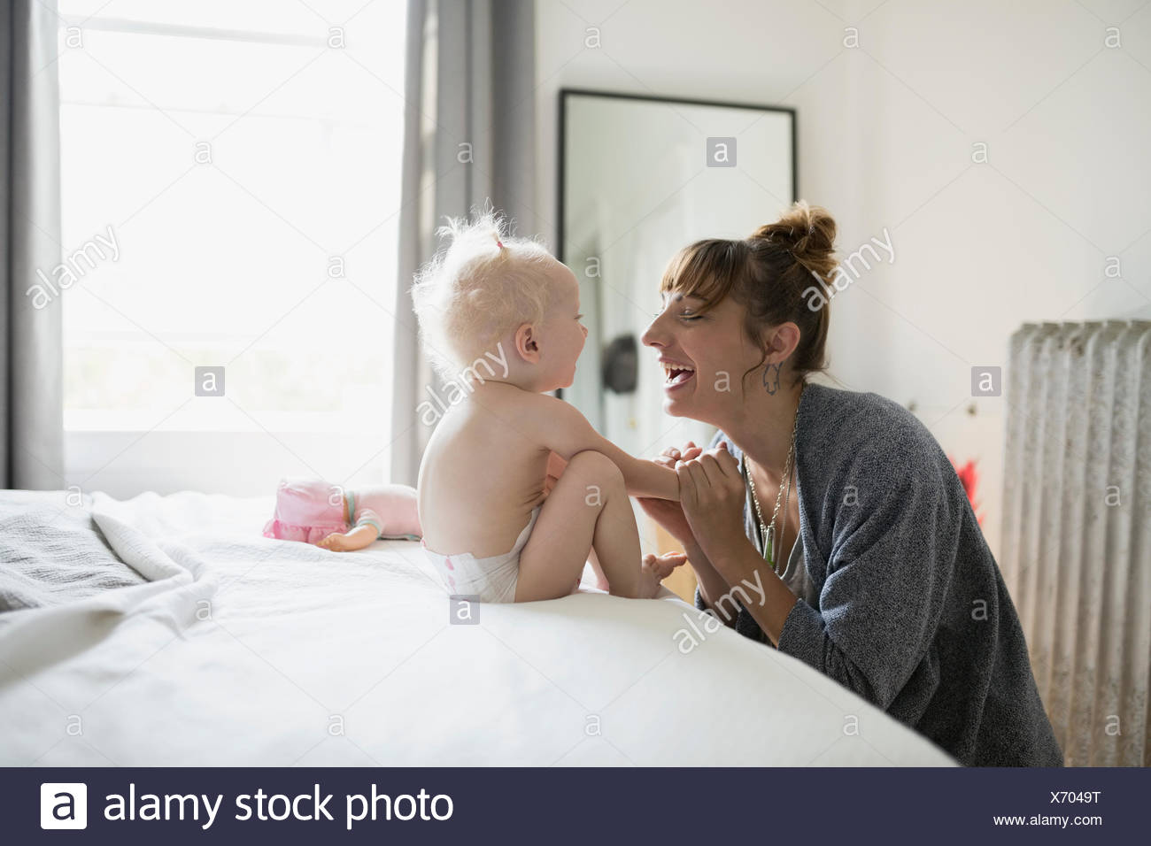 Playful mother and baby daughter face to face on bed - Stock Image