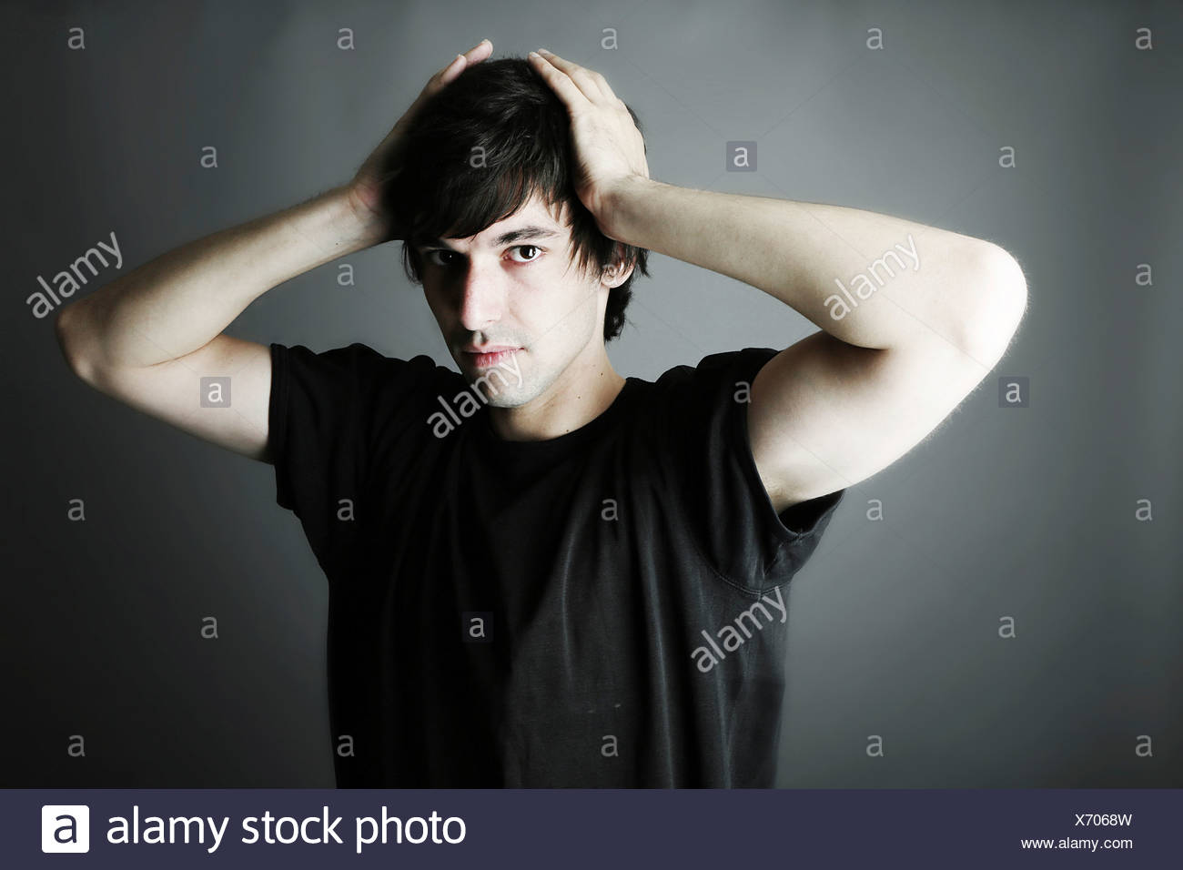 Portrait of young man against grey background, close up - Stock Image