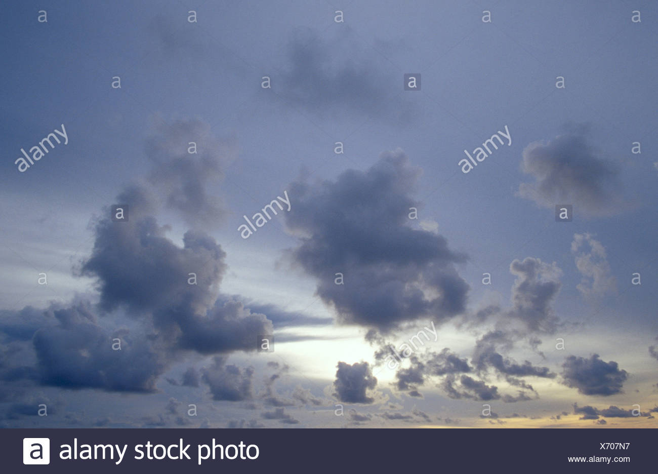 Wispy tropical storm clouds in the afterglow of sunset. - Stock Image