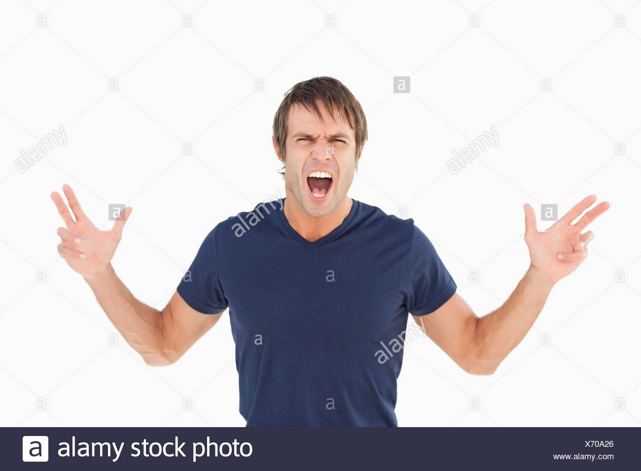 Furious man shouting while raising his arms - Stock Image