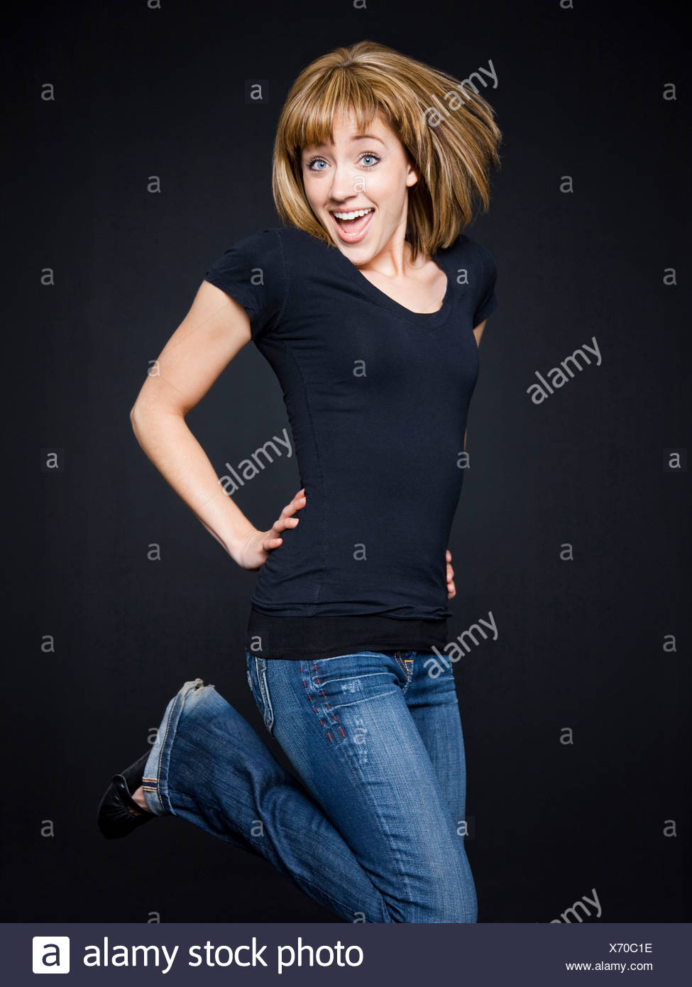Young cheerful woman jumping, studio shot - Stock Image