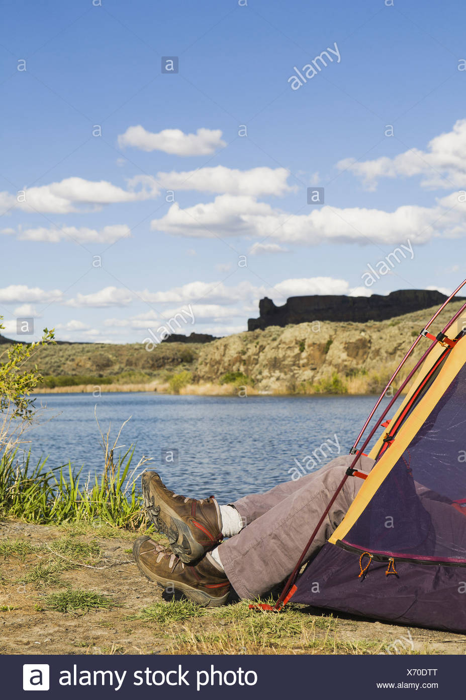 A small tent pitched by the shores of the Sun Lakes in Sun Lakes State Park A man's feet in loafers sticking out - Stock Image