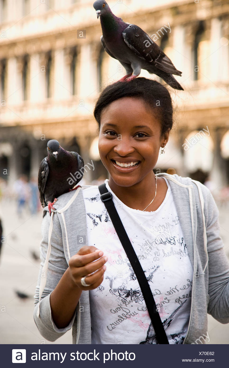 Young woman with birds on her head and shoulder. - Stock Image