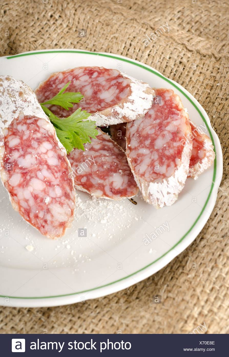 Sausage on a plate on the fabric. - Stock Image