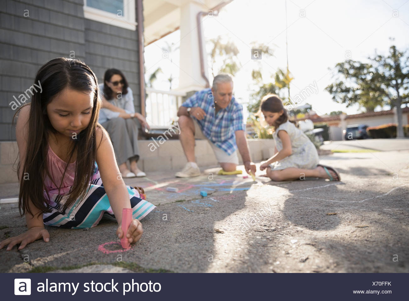 Multi-generation family drawing with sidewalk chalk in driveway - Stock Image