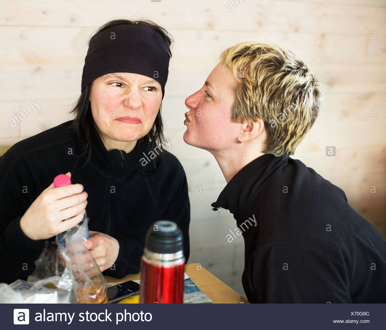 One woman faking a kiss one woman making a face Sweden. - Stock Image