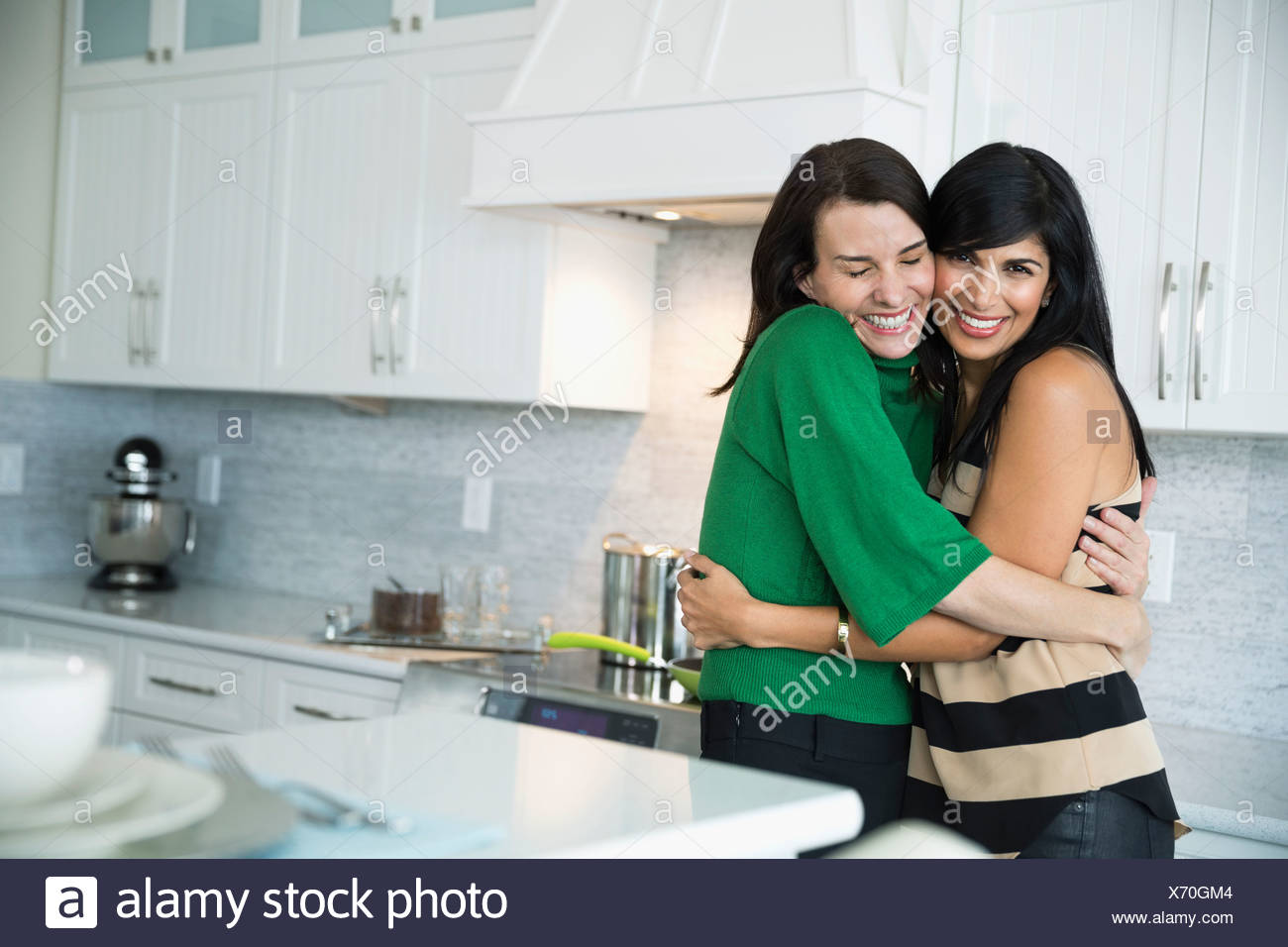 Portrait of happy mature woman embracing female friend in domestic kitchen - Stock Image