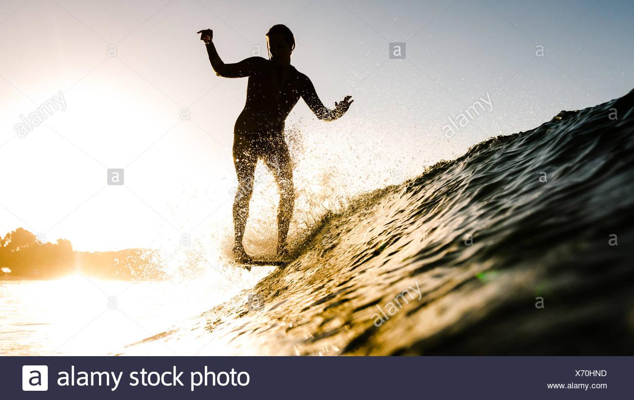 Woman surfing at sunset, Malibu, California, USA - Stock Image