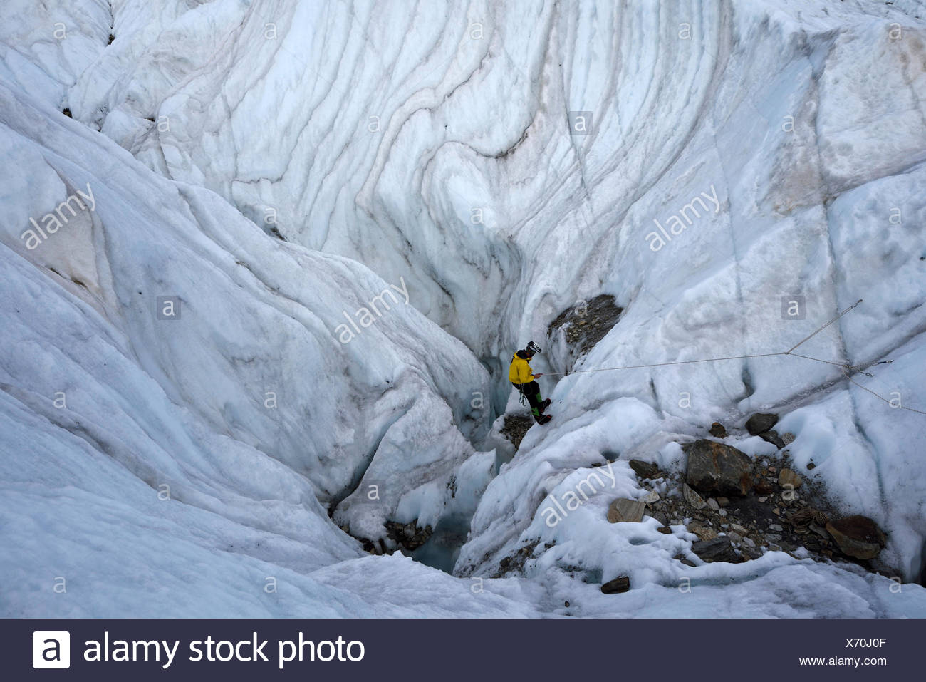 Italian cave explorer and Rolex Award 2014 winner Francesco Sauro rigs the ropes and begins his descent down into a large moulin. Stock Photo