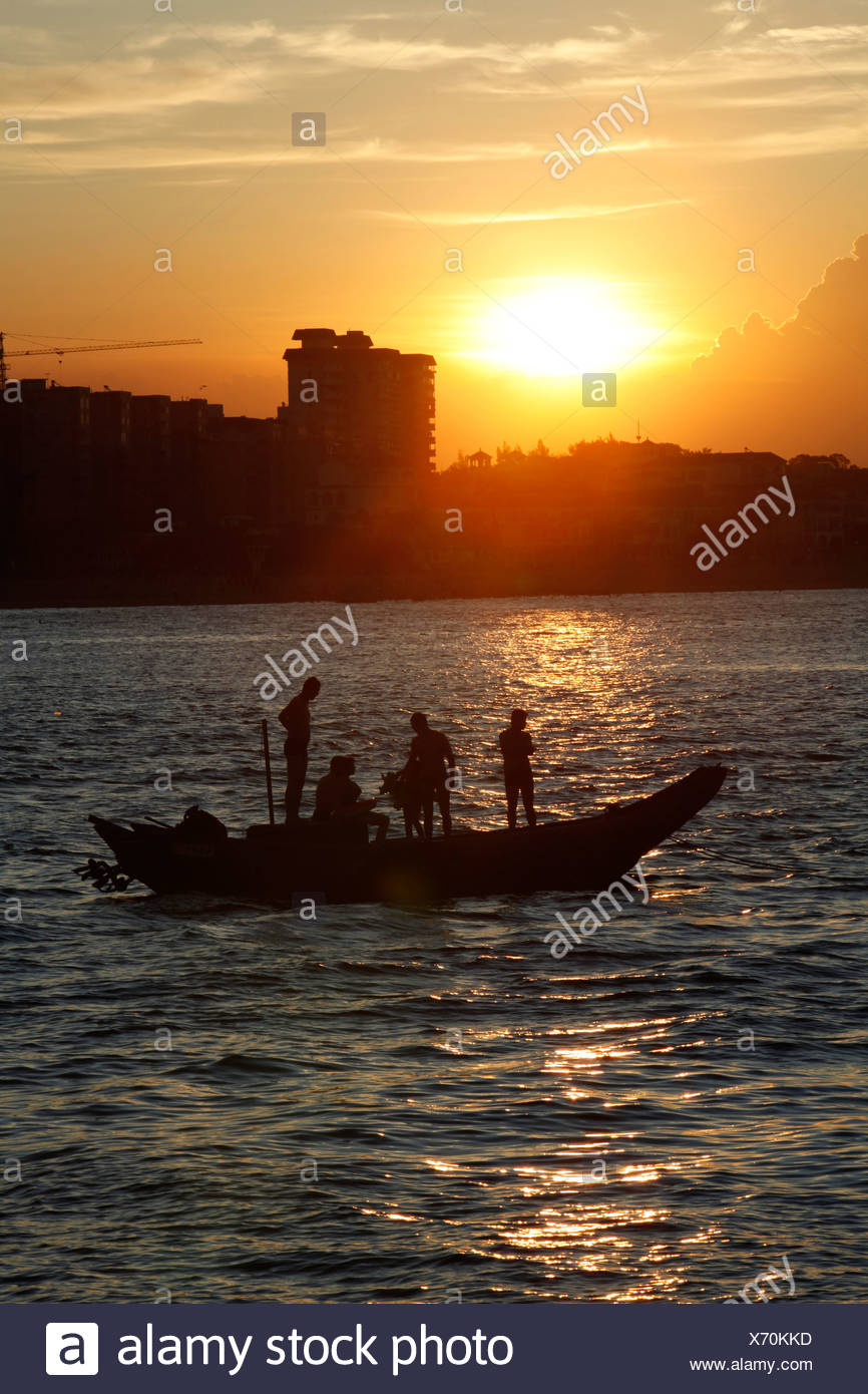 People on a boat at sunset in a bay of the South China Sea, Xiamen, Fujian Province, China, Asia - Stock Image