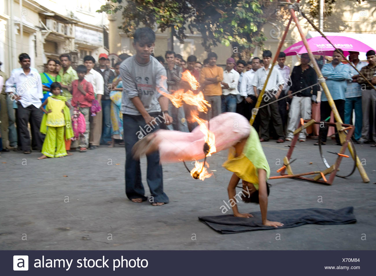 Boy jumping through iron ring, fire performance in Kala ghoda festival art fair ; Bombay Mumbai ; Maharashtra ; India - Stock Image
