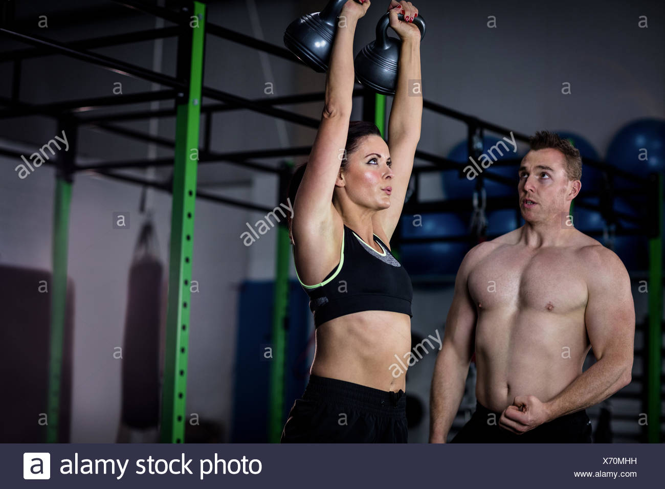 Trainer assisting a woman while exercising with kettlebell - Stock Image