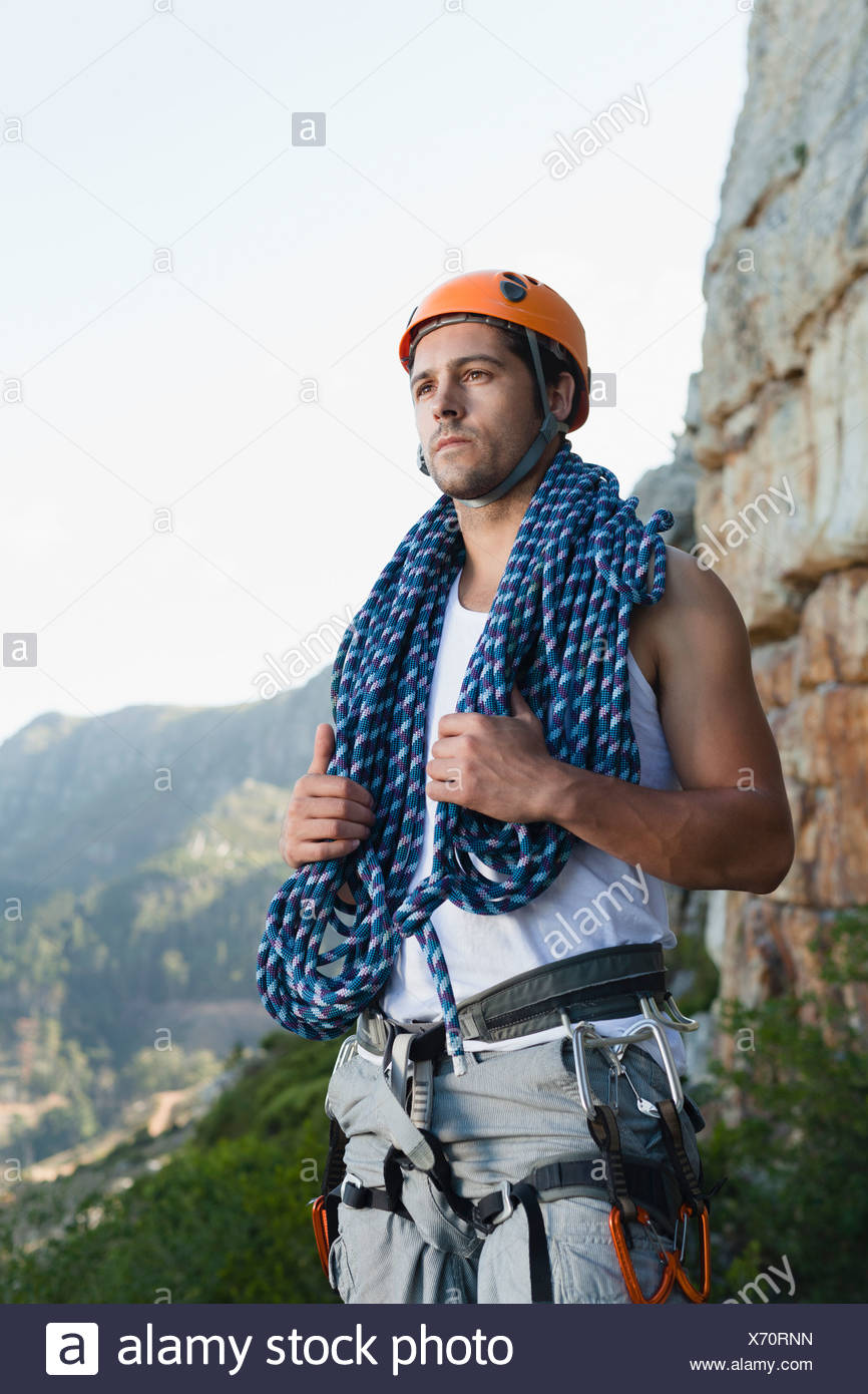 Climber holding coiled rope on mountain - Stock Image