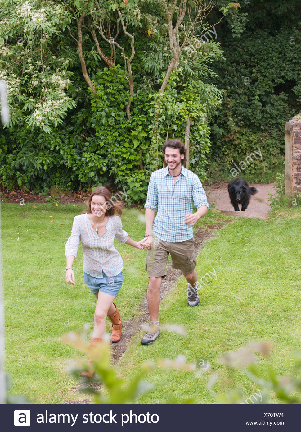 couple running along path towards house - Stock Image