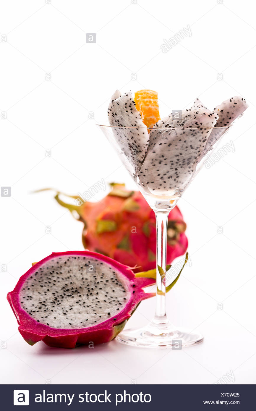 White fruit wedges of a pitaya assorted in a glass and adorned with a mandarine slice. Next to it, the fruit pulp of a halved dragon fruit is shining out of its vibrant violet skin. - Stock Image
