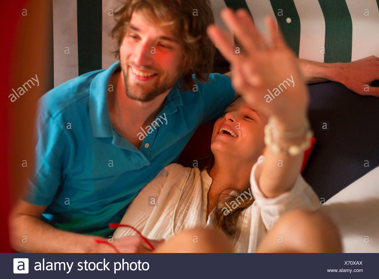 Carefree young couple lounging in bar - Stock Image