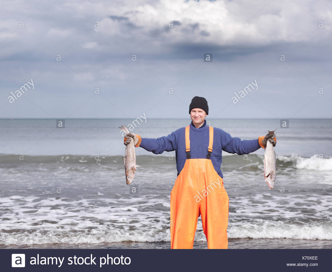 Fisherman on shore holding fish - Stock Image