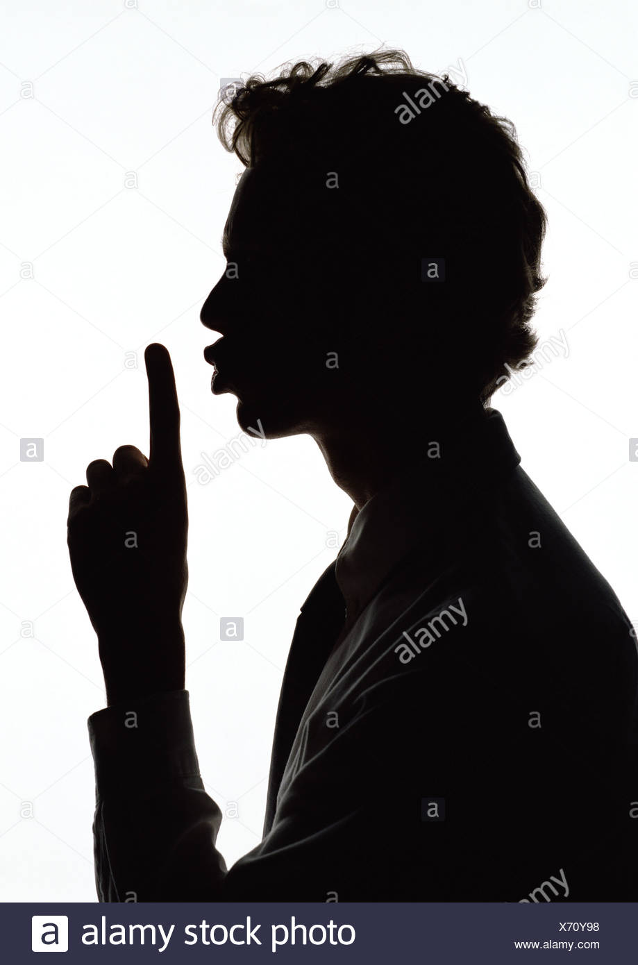 Man holding finger out in front of lips, silhouette. - Stock Image