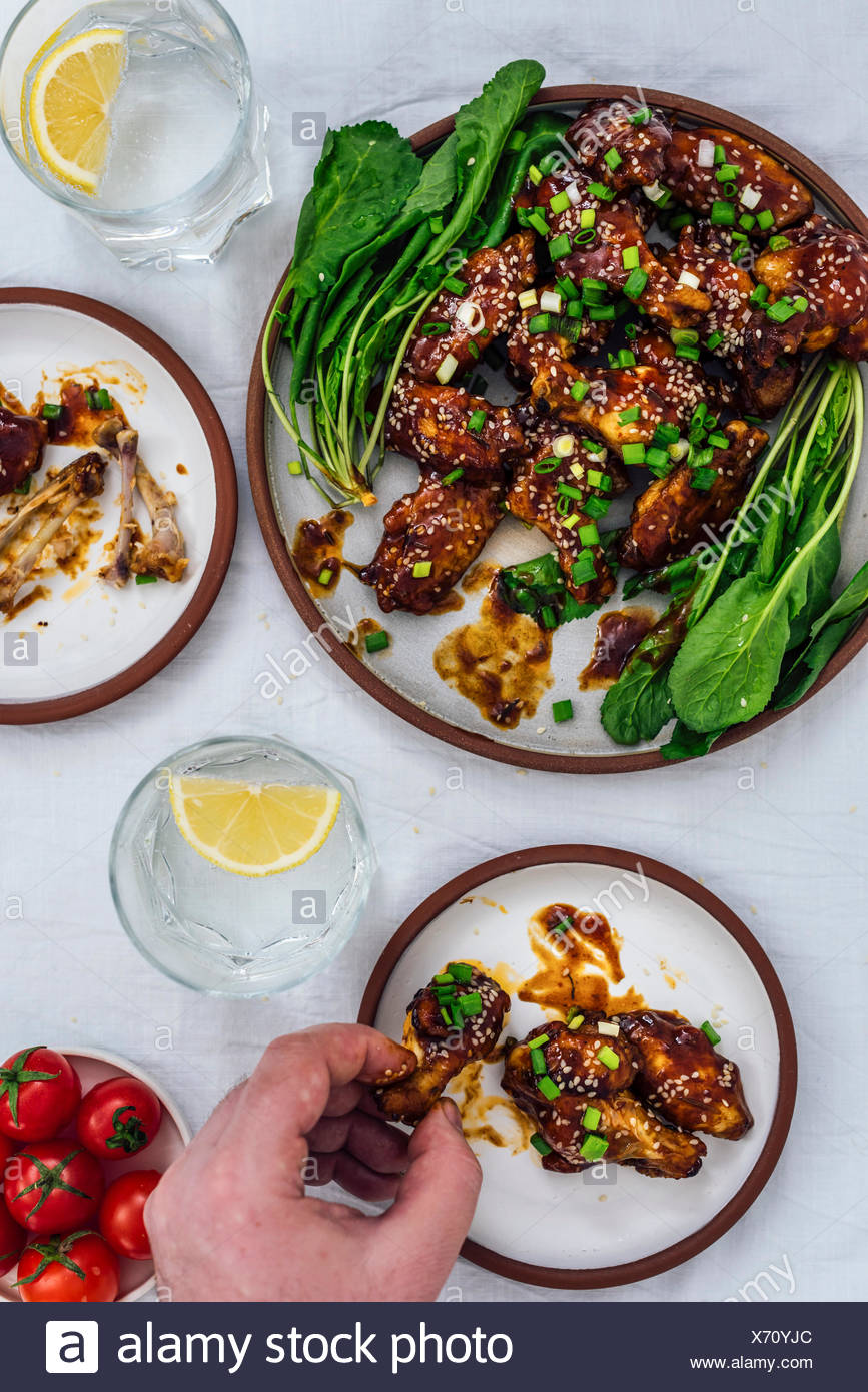 Oven-baked chicken wings with a sticky sauce and sesame seeds served with herbs on one large plate and two small plates accompanied by soda with lemon - Stock Image
