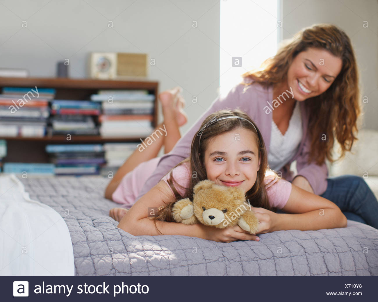 Mother and daughter relaxing on bed - Stock Image