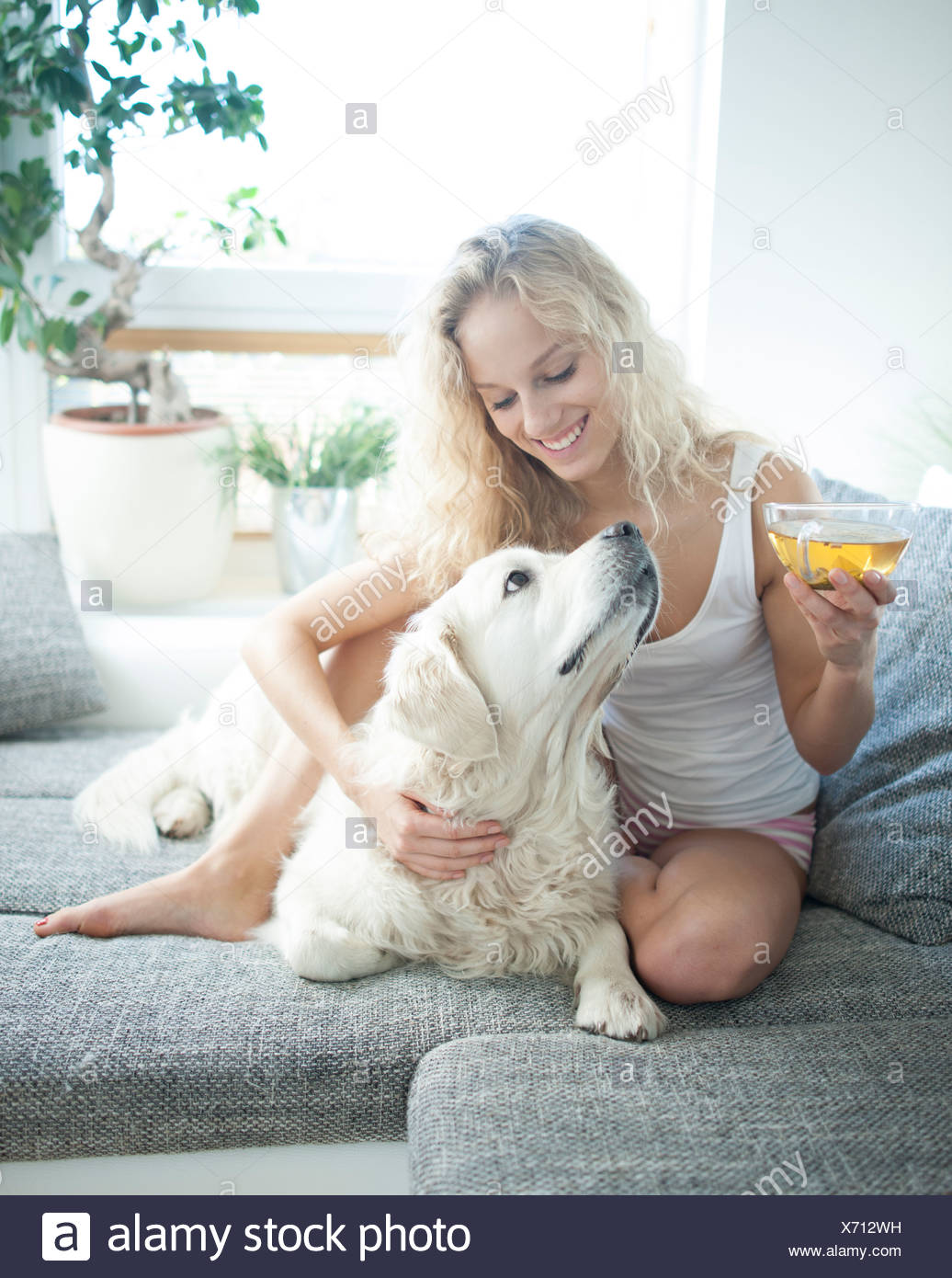 Beautiful woman holding tea cup while touching dog on sofa - Stock Image