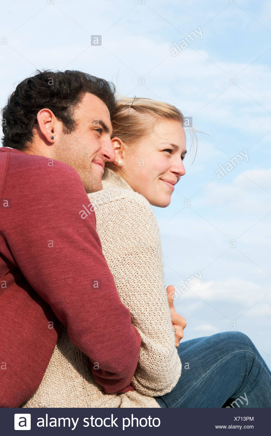 Sweden, Vastra Gotaland, Kallandso, Young couple relaxing on lakeshore - Stock Image
