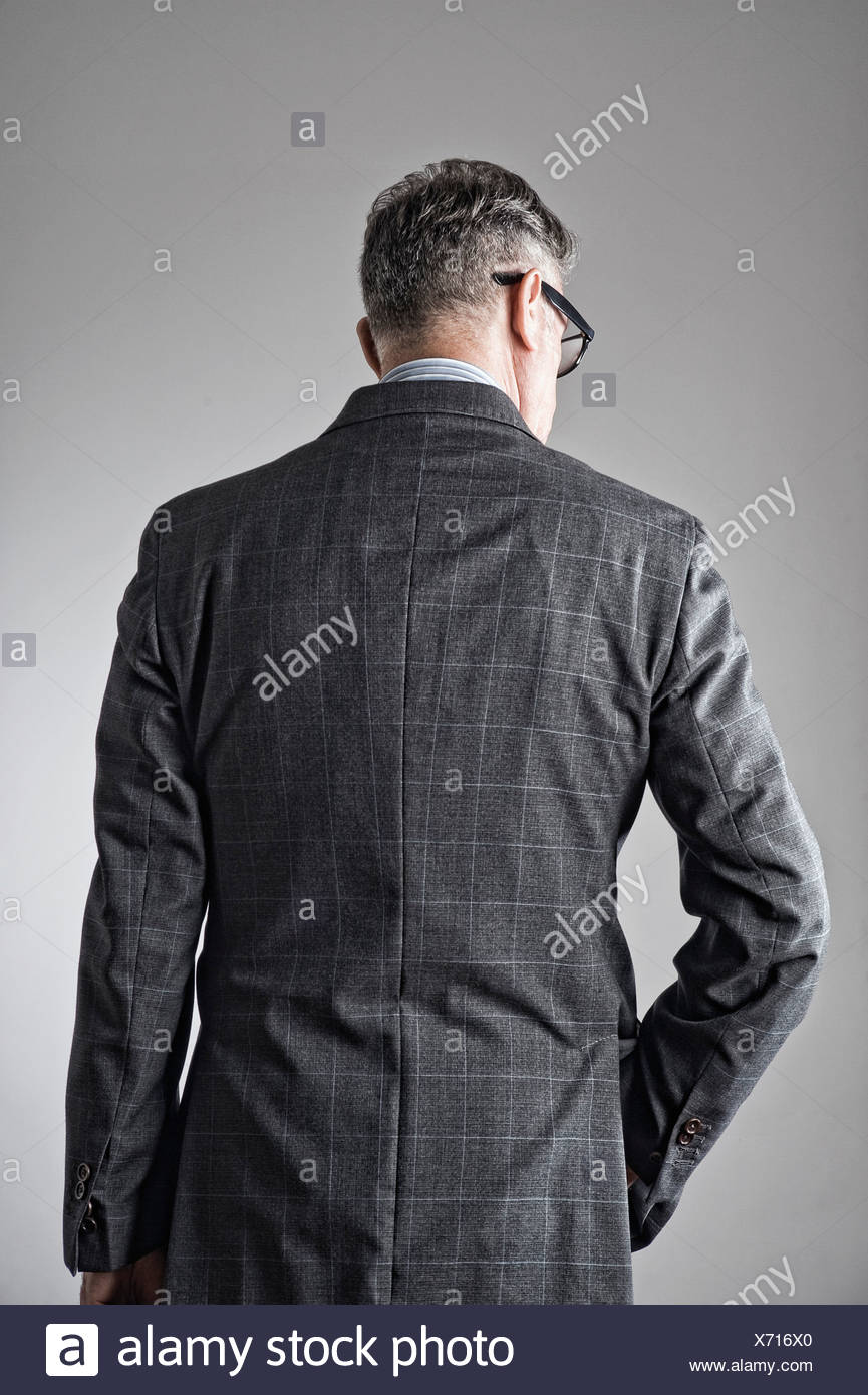 Portrait of senior man, wearing suit, rear view - Stock Image