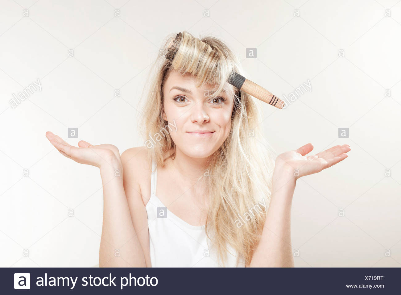 Young woman with hairbrush fooling around - Stock Image