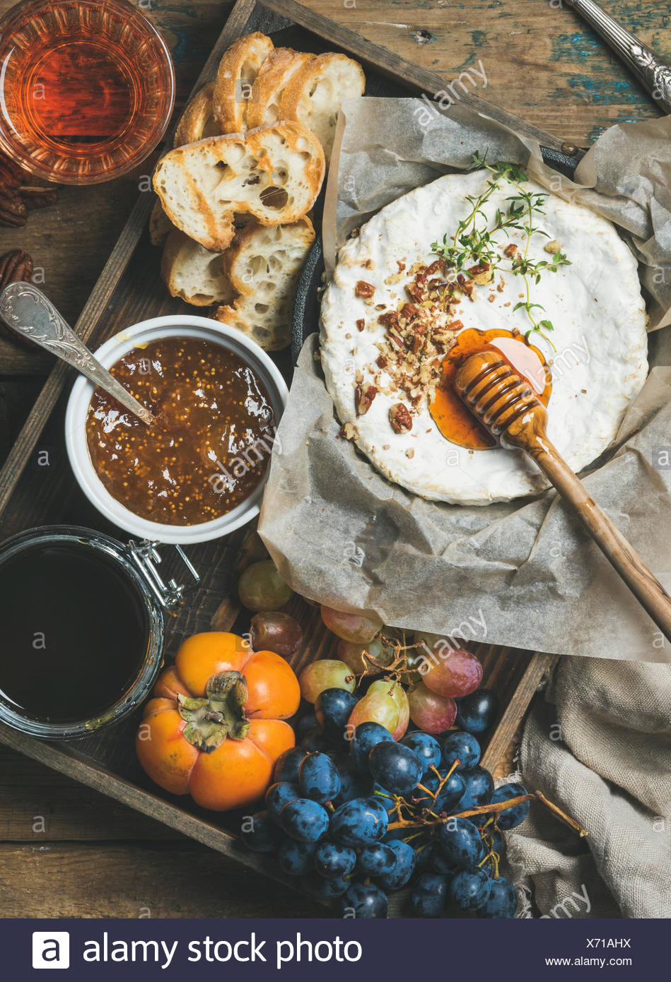 Cheese, fruit and wine set. Camembert in small pan with nuts and herbs, grapes, persimmon, fig jam, honey, baguette slices and g - Stock Image