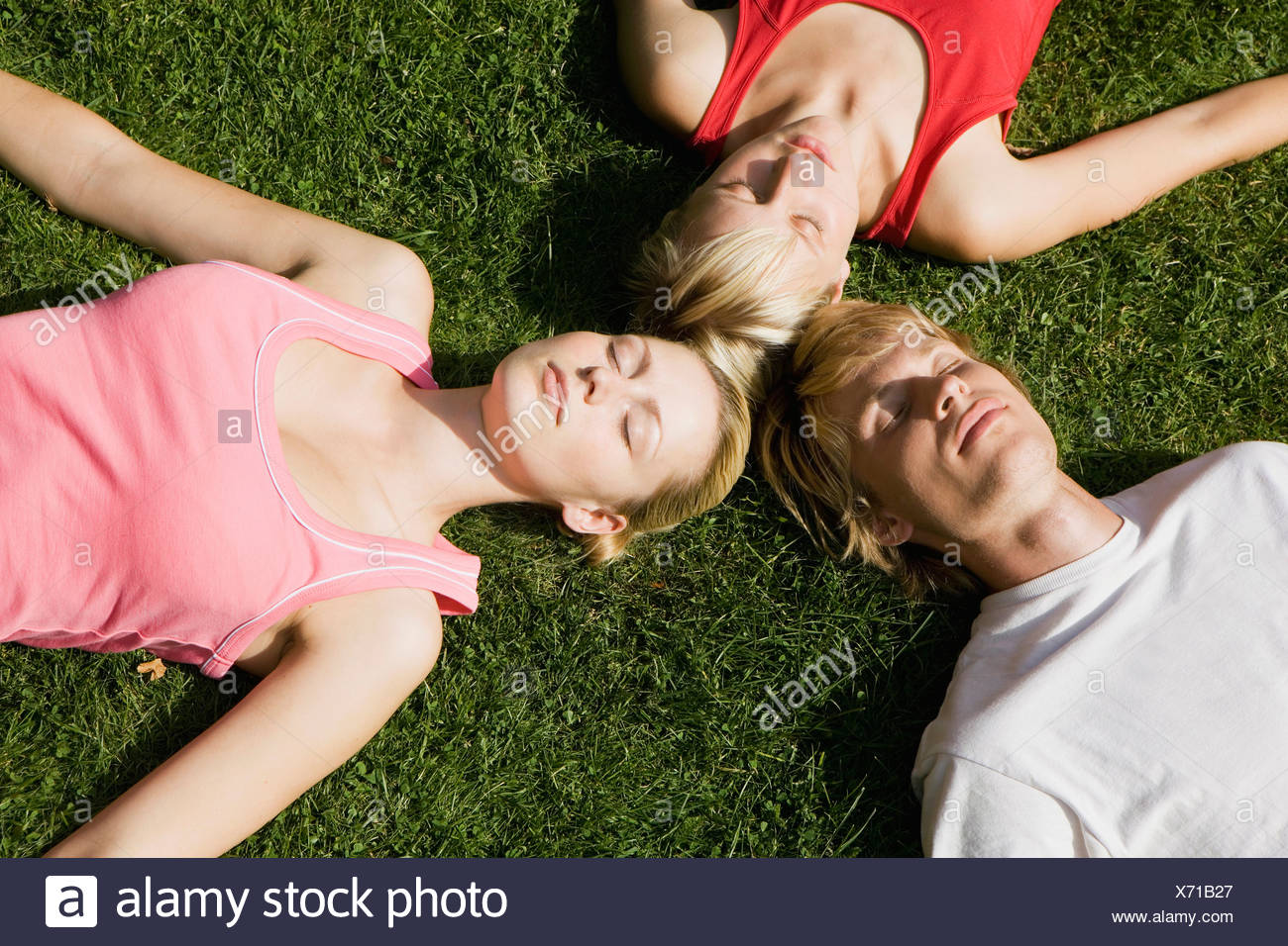 Germany, Berlin, Three persons lying on lawn, elevated view - Stock Image