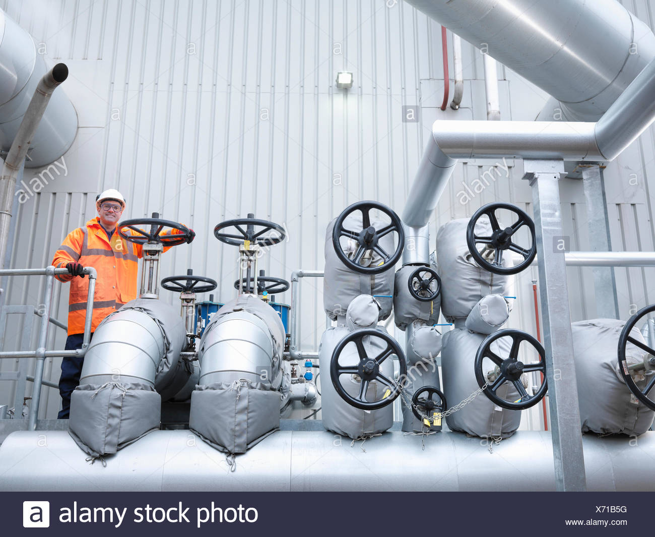 Worker standing by valves of gas fired power station - Stock Image