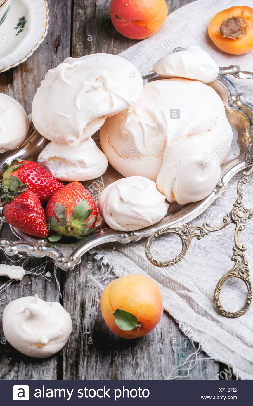 Homemade meringue with apricot and strawberry served on vintage tray over wooden table. - Stock Image