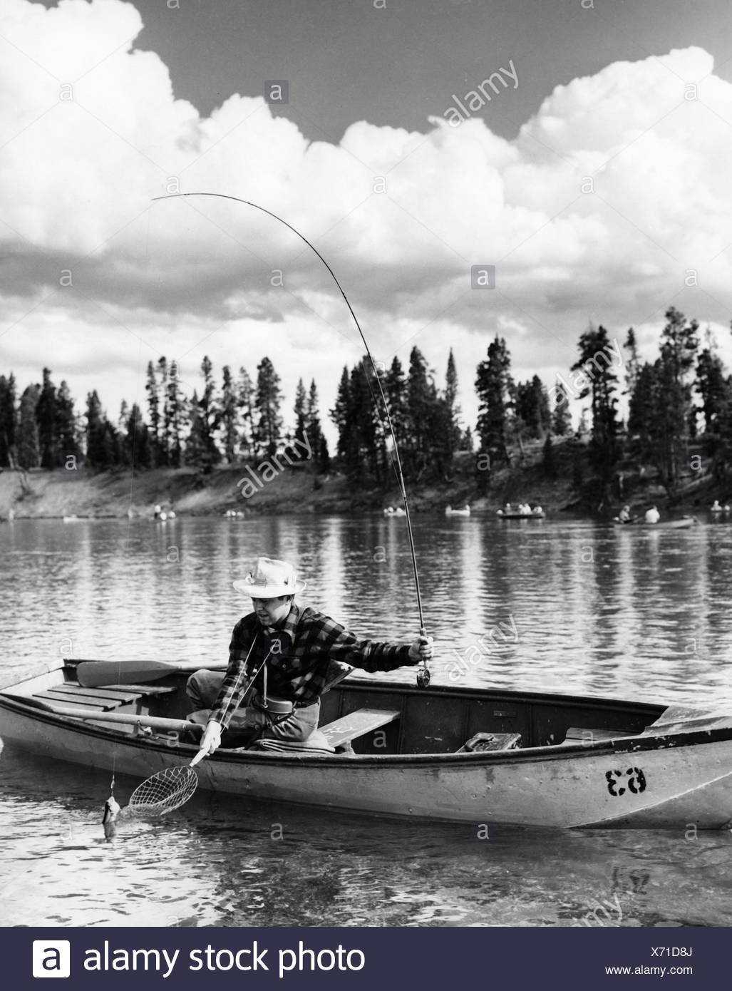 Mid adult man sitting on a rowboat and fishing in a lake - Stock Image