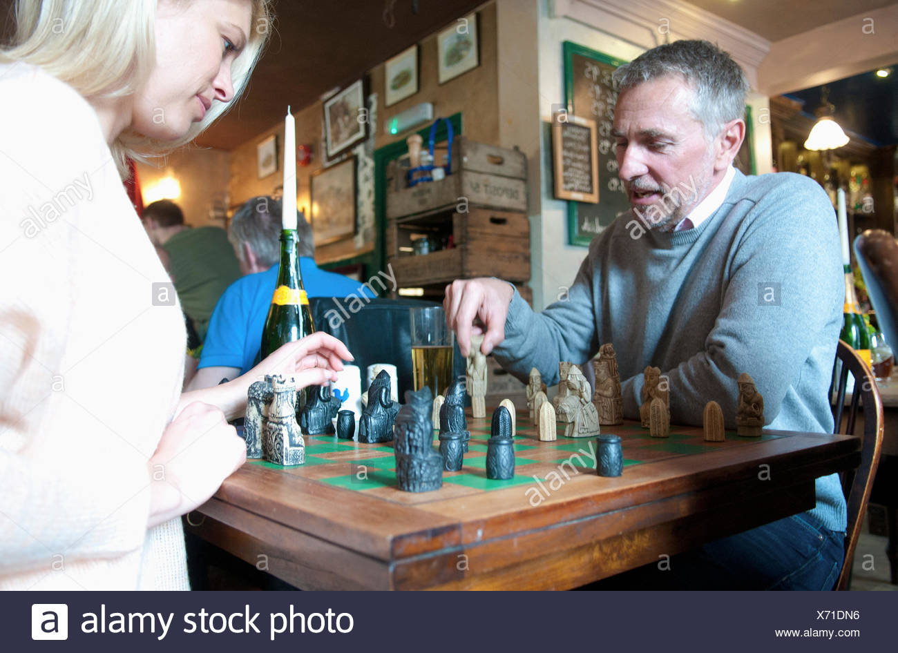 Couple playing chess in pub - Stock Image