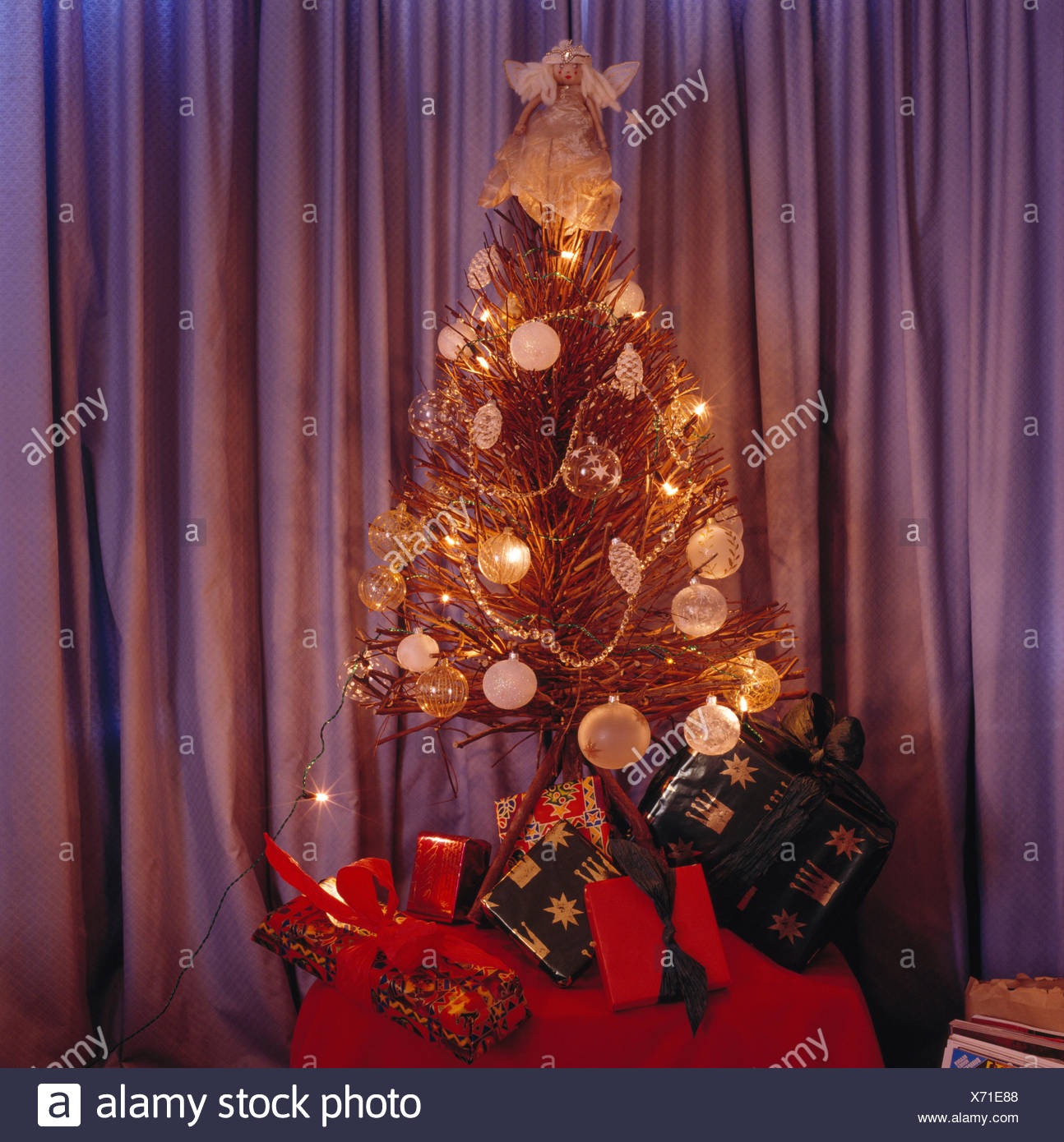 Twig Christmas tree with glass baubles and lights on a table with wrapped presents - Stock Image