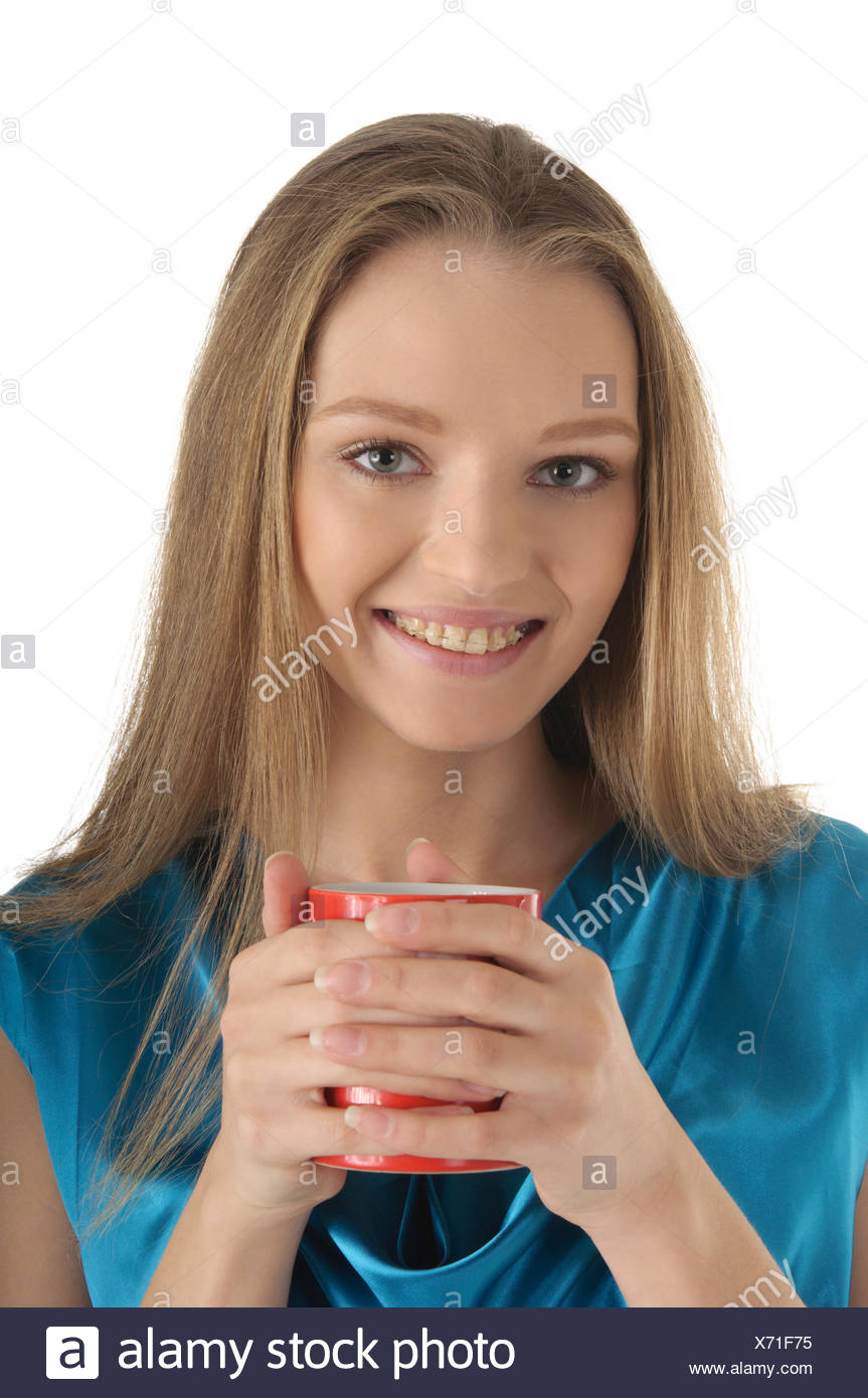 Woman with brackets on teeth and cup - Stock Image