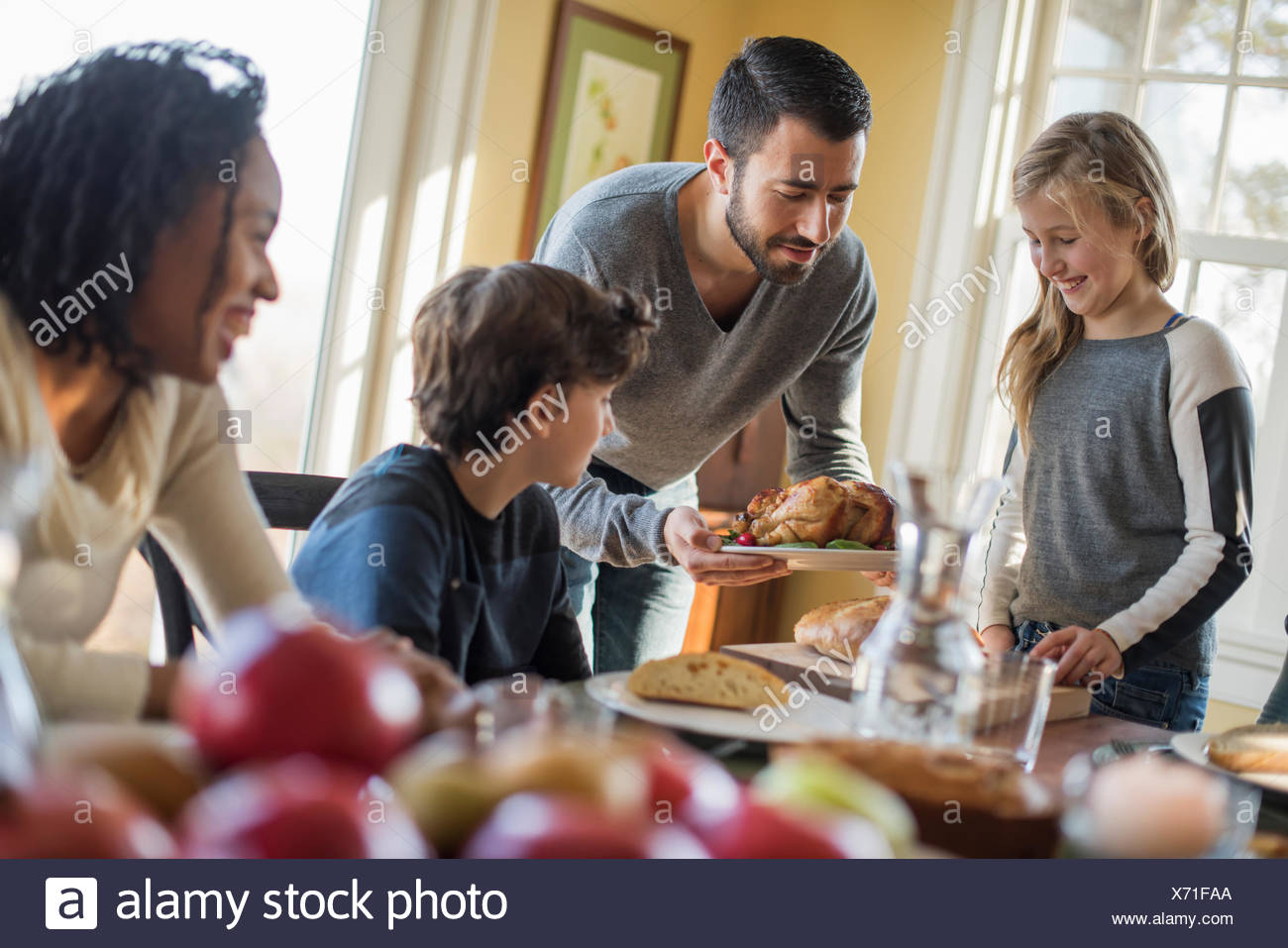 Adults and children gathered around a table for a meal. - Stock Image
